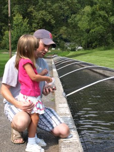 Eric Molitoris and his daughter, Avery, feed the trout at the Fish Hatchery.